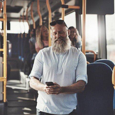 Mann im Bus schaut entspannt auf sein Smartphone